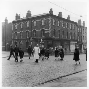 In Liverpool, a Lollipop Lady Helps Children Cross a Cobbled Street by Henry Grant