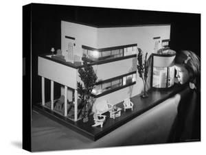 Little Girl Looking Into a Modern Doll House Being Sold at F.A.O. Schwarz by Herbert Gehr