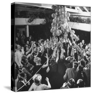 People Reaching For the Balloons at the Palm Beach Party by Herbert Gehr