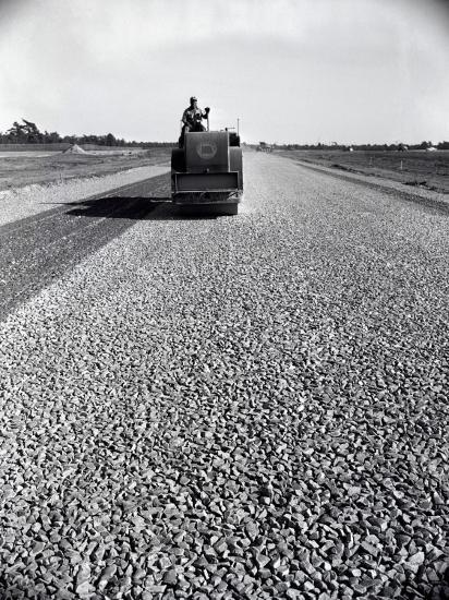 Highway Construction Worker Operating Heavy Machinery on Loose Gravel Road-H^ Armstrong Roberts-Photographic Print