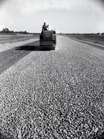 https://imgc.artprintimages.com/img/print/highway-construction-worker-operating-heavy-machinery-on-loose-gravel-road_u-l-q10bqo80.jpg?p=0