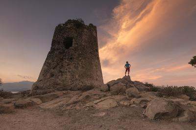 Hiker Admires Sunset from the Stone Tower Overlooking the Bay, Porto Giunco, Villasimius-Roberto Moiola-Photographic Print