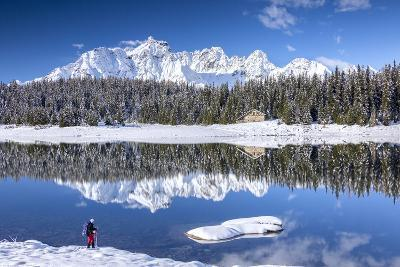 Hiker Admires the Snowy Peaks and Woods Reflected in Lake Palu, Malenco Valley, Valtellina, Italy-Roberto Moiola-Photographic Print
