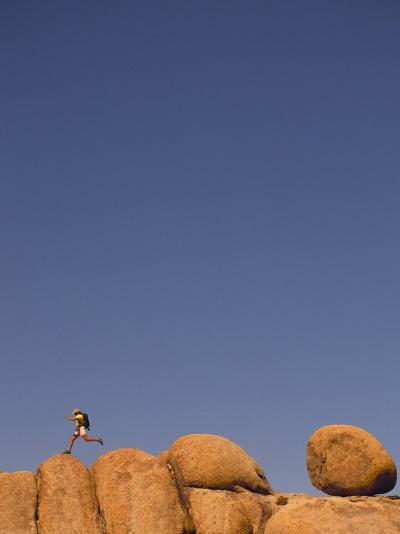 Hiker Jumping on Rocks-Bill Hatcher-Photographic Print