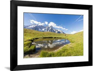 Hiker with dog admires the peaks of Mont De La Saxe reflected in water, Courmayeur, Aosta Valley, I-Roberto Moiola-Framed Photographic Print