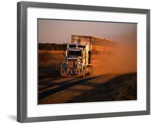 Road Train Driving along Dusty Road, Kynuna, Australia by Holger Leue