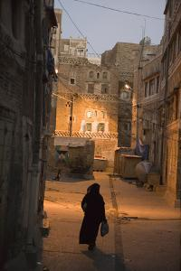 Woman Walking in Old Town, Dusk, San'a, Yemen, Middle East by Holger Leue