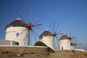 Greece, Mykonos. Windmills along the water by Hollice Looney
