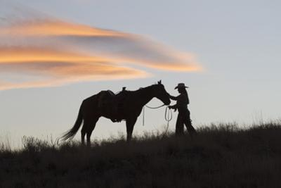 USA, Wyoming, Shell, The Hideout Ranch, Silhouette of Cowgirl with Horse at Sunset by Hollice Looney