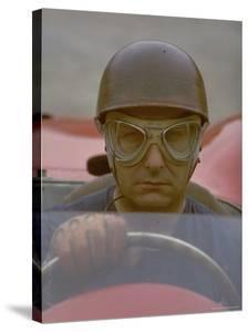 Argentine Auto Racer Juan Manuel Fangio Sitting at Wheel of Race Car at Las Mans by Howard Sochurek