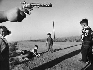 """Boy's Hand Holding a Toy Six Shooter Pistol During a Game of """"Cops and Robbers"""" by Howard Sochurek"""