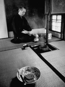 Old Monk Sitting in Cell Meditating and Performing Tea Ceremony by Howard Sochurek