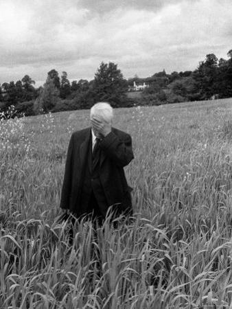 Poet Robert Frost Standing in Oxford Field with His Hand over His Face