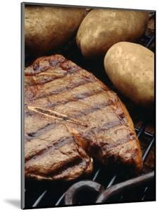Steak and Potato on Grill by Howard Sokol