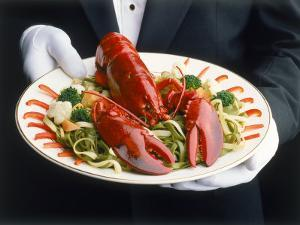 Waiter Serving Plate of Lobster by Howard Sokol