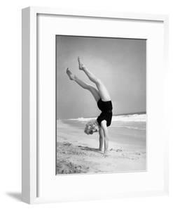 Woman Does Handstand on the Beach (B&W) by Hulton Archive
