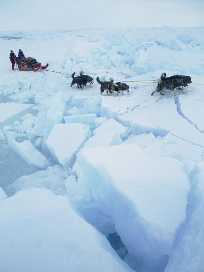 Huskies Carry a Sled Across Broken Ice During an Expedition Traversing the North Pole-Gordon Wiltsie-Photographic Print