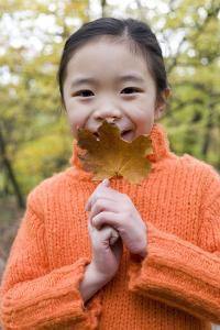 Girl Holding An Autumn Leaf by Ian Boddy