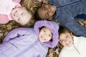Smiling Children Lying on Autumn Leaves by Ian Boddy