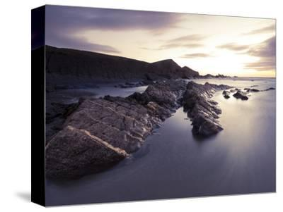 Long Exposure of Waves Moving over Rocks on Crackington Haven Beach at Sunset, Cornwall, England