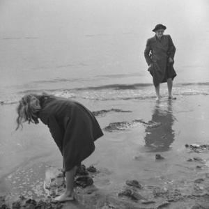 Girl Playing in the Sand while an Older Woman Gets Her Feet Wet in the Ocean at Blackpool Beach by Ian Smith