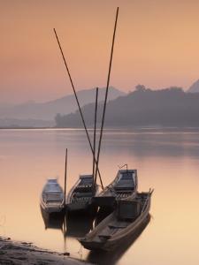 Boats on Mekong River at Sunset, Luang Prabang, Laos by Ian Trower