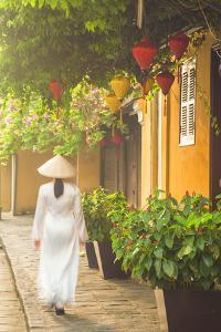 Woman Wearing Ao Dai Dress Walking Along Street, Hoi An, Quang Ham, Vietnam by Ian Trower