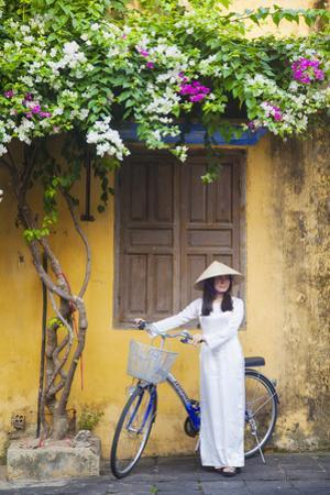 Woman Wearing Ao Dai Dress with Bicycle, Hoi An, Quang Ham, Vietnam by Ian Trower