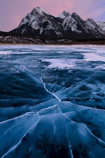 Ice cracks along Abraham Lake in Banff, Canada with purple clouds and scenic mountains-David Chang-Photographic Print