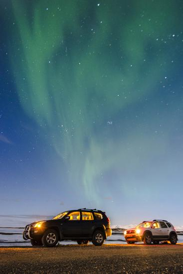 Iceland, Europe. Cars with lights on at night under a starry sky and the northern lights.-Marco Bottigelli-Photographic Print