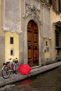 Red Umbrella and Bicycle at the Door, Florence by Igor Maloratsky