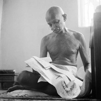 Indian Leader Mohandas Gandhi Reading as He Sits Cross Legged on Floor, at Home-Margaret Bourke-White-Premium Photographic Print