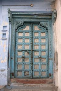 Blue-painted door, Jojawar, Rajasthan, India. by Inger Hogstrom