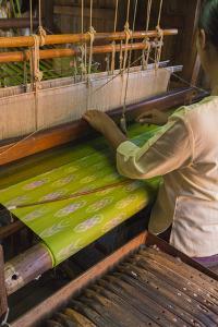 Myanmar. Shan State. Inle Lake. Woman weaving silk at a wooden loom. by Inger Hogstrom