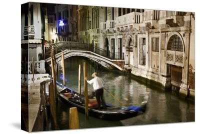 A Gondolier in a Quiet Canal At Night in Venice, Italy