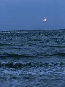 A Twilight Shot of Waves Coming into Shore with the Moon in the Background by Ira Block