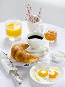 Breakfast with Coffee, Croissant, Fried Egg, Jam and Orange Juice by Ira Leoni