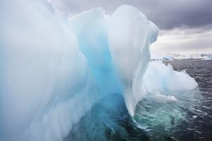 Close Up of a Blue Iceberg under a Stormy Gray Sky by Ira Meyer