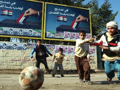 "Iraqi Boys Play Soccer Below the Poster Reading ""To Grant Iraqi Children Better Iraq""--Photographic Print"
