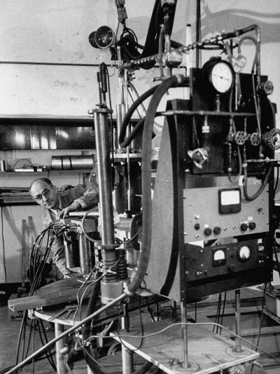 Italian Physicist Enrico Fermi Peering Out from Behind Large, Complicated Machinery in Laboratory-Ralph Morse-Premium Photographic Print