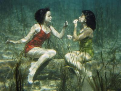 Performing swimmers put on lipstick underwater by J^ Baylor Roberts