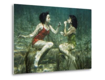 Performing swimmers put on lipstick underwater