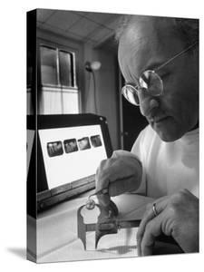 Dentist Dr. Harland Measuring Tooth to Be Used in Medical Dentistry by J. R. Eyerman