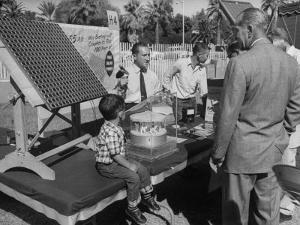 Salesman Demonstrating Solar Battery at the International Conference on Solar Energy by J. R. Eyerman