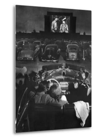 Young Couple Snuggling in Convertible as They Watch Large Screen Action at a Drive-In Movie Theater