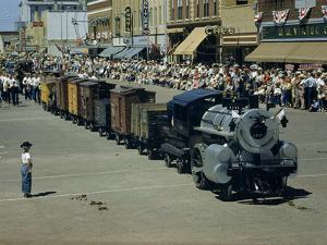 People Watch a Miniature Train Parade on Main Street by Jack Fletcher