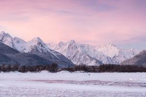 Pink Dawn over Snowy Mountains with a Frozen River in the Foreground by Jak Wonderly