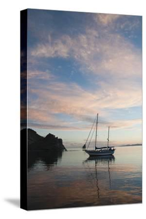 A Sailboat Anchored in a Bay During a Colorful Sunset