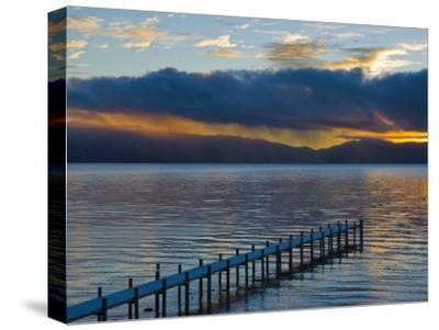 Snow Covered Pier on Lake Tahoe with Dramatic Sunrise Light