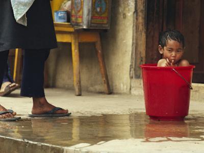 Bhutanese Boy Bathing in a Bucket by James L. Stanfield